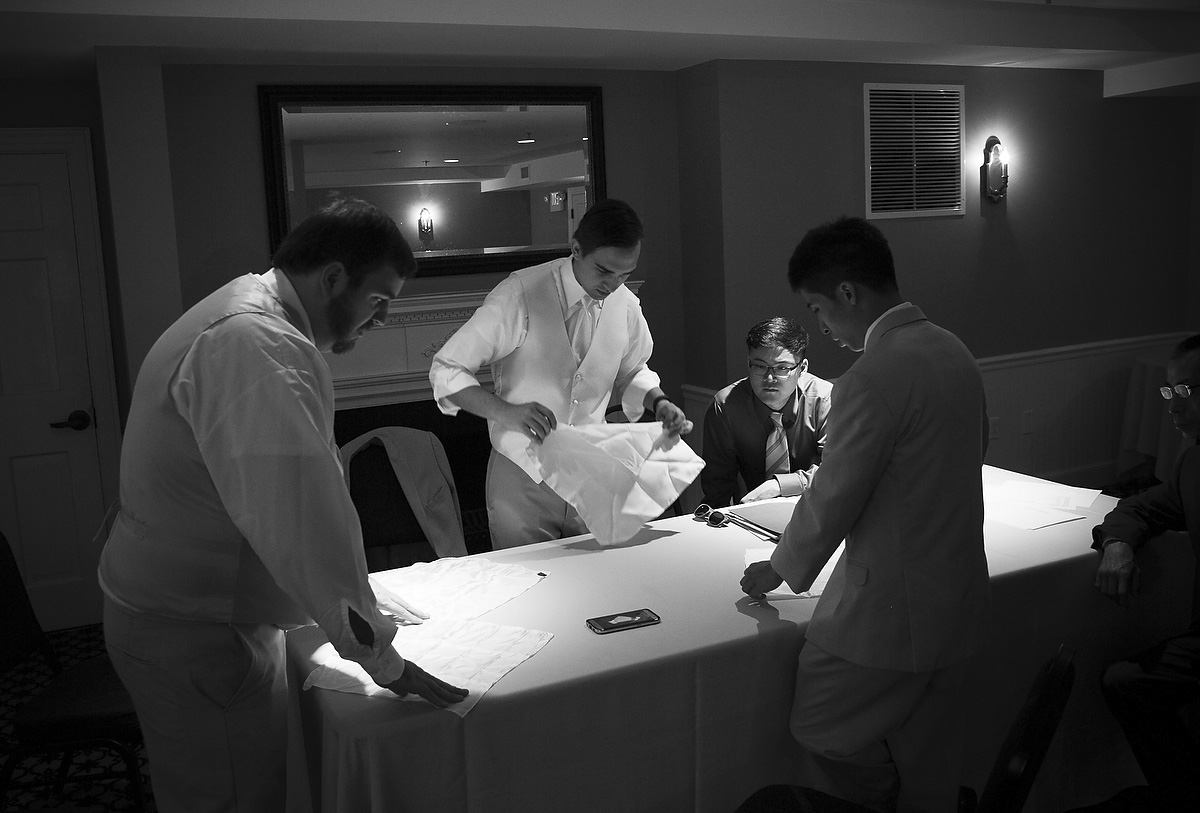 groomsmen learn to fold hankerchiefs using a youtube video