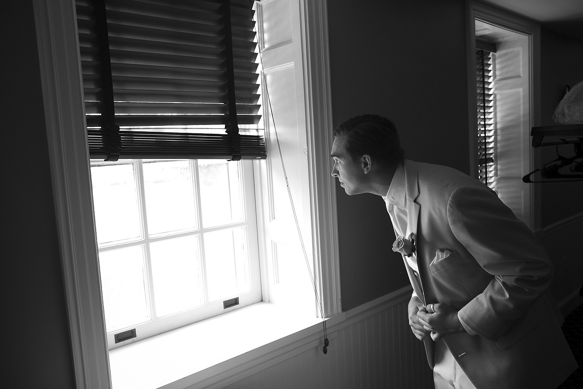 groom looks out window before his wedding at top of the bay