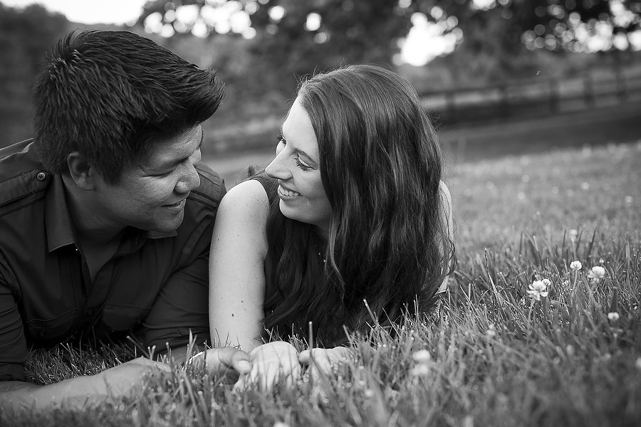 couple lying on grass during engagement portraits