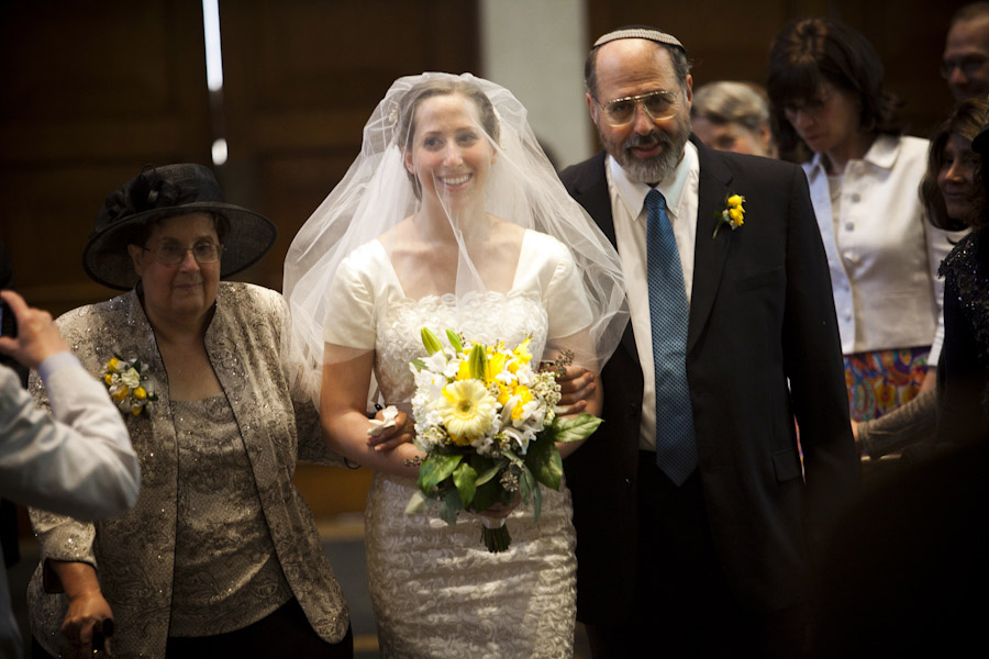 bride walks down the aisle with her parents