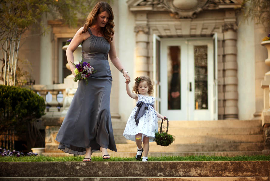 flower girl walks down the aisle with her mother