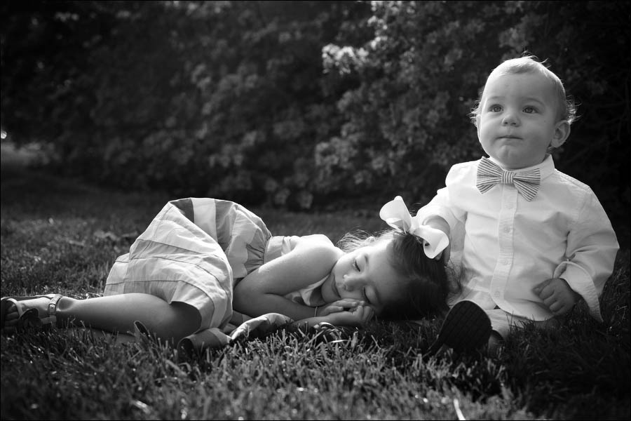 little girl napping on the grass with her baby brother