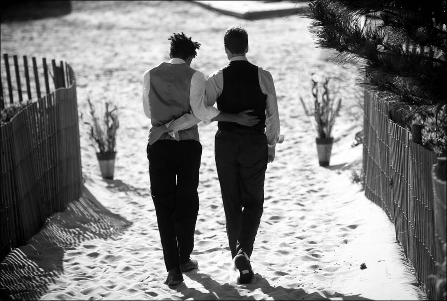 patrick and brian walk down the beach after their wedding